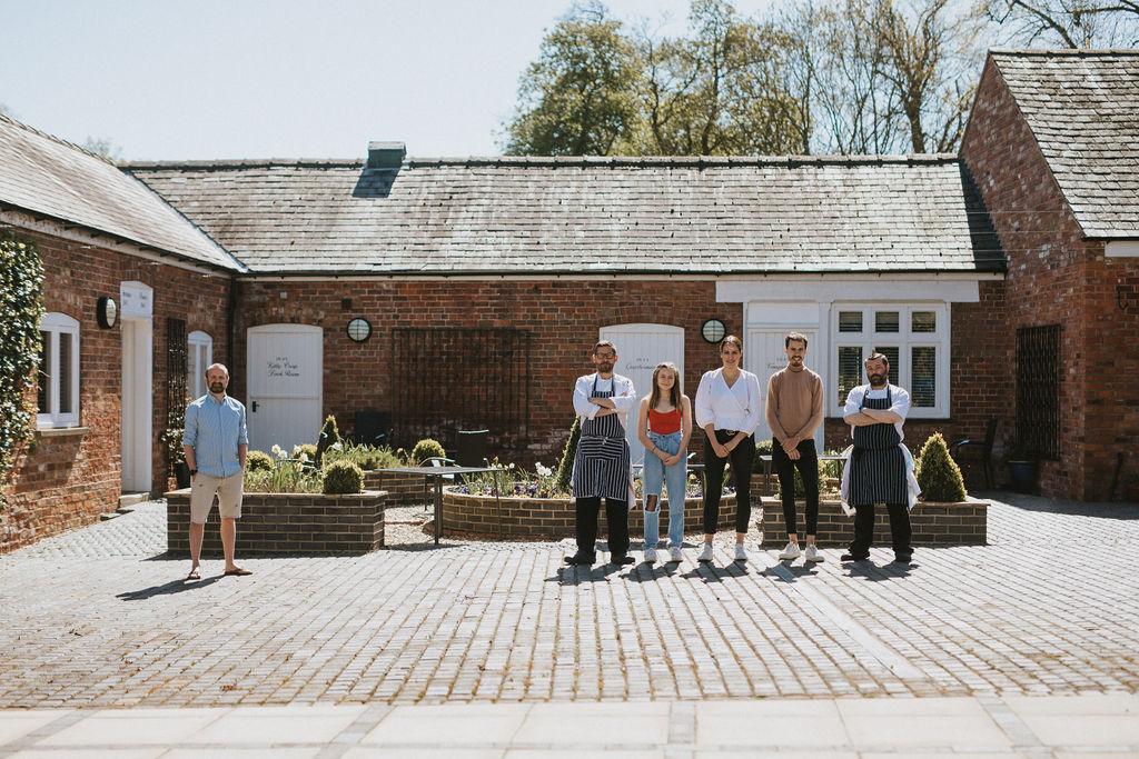 Healing Manor Team Photo shown in Healing Manor Courtyard