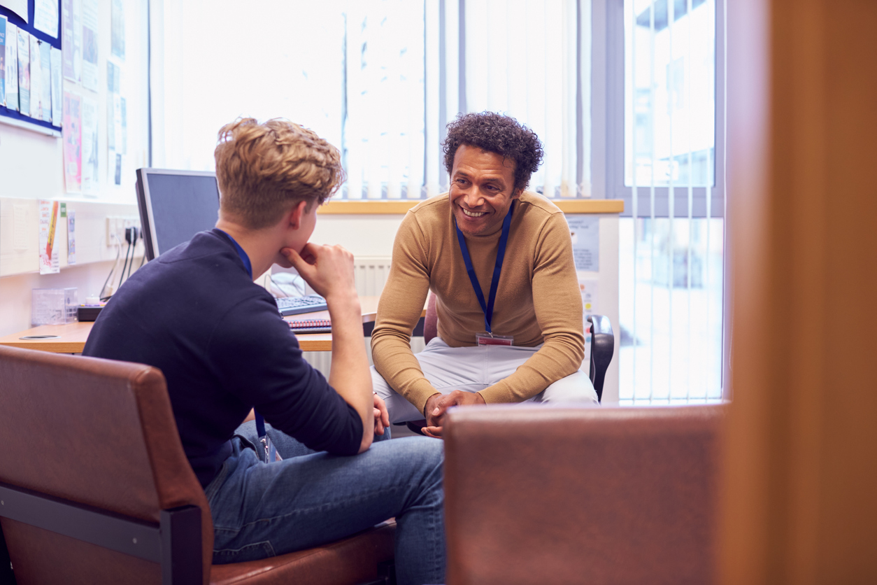 Male College Student Meeting With Campus Counsellor Discussing Mental Health Issues