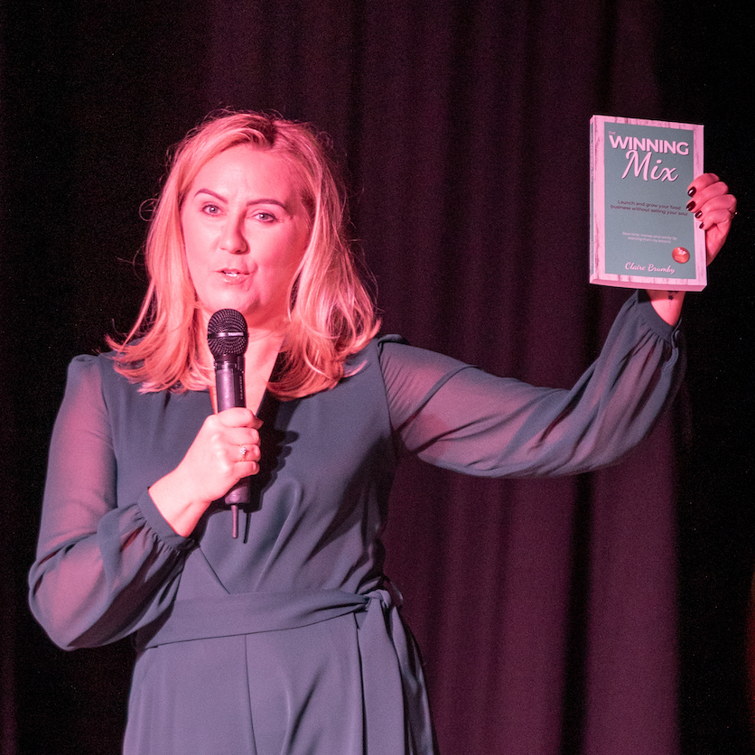 """Claire Brumby holding a copy of her book """"The Winning Mix"""""""