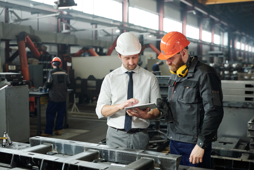 Young man in hardhat and bearded engineer discussing technical sketch