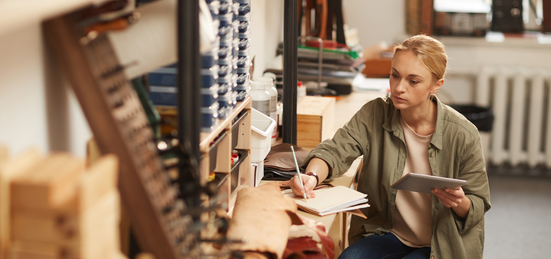 Horizontal high angle portrait of serious young woman sitting at table in craft workshop holding tablet PC and making notes in notebook